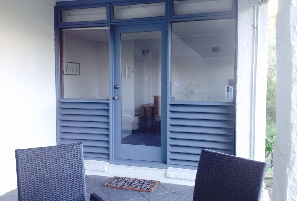 Private entrance to the apartment with garden furniture for a relaxing morning breakfast.