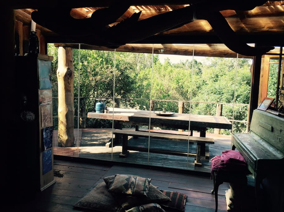 Sliding glass doors to the Wooden deck- opening the house out to the forest outside with an outside dining area and view over the tsitsikamma forest