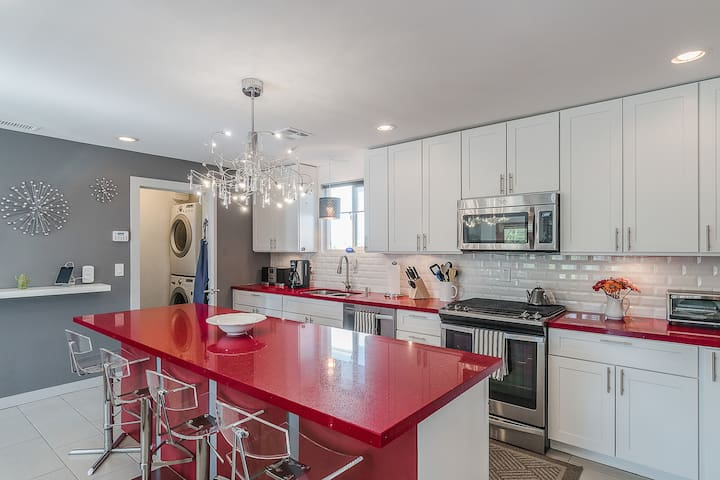Fun design accents include sleek red countertops in the kitchen.