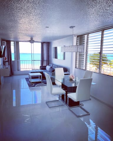 Milly 787-460-1794 Beautiful !!  Spacious and Modern, Just remodeled. This is the livingroom and dining areas with an Amazing Ocean front View!!  Everything is New! All white...Fully equipped!
