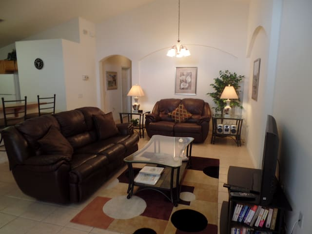 Lounge area with large cable TV, reclining leather sofas and chairs.