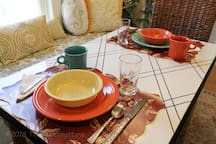 Eat-in kitchen w/ bench seat, dishwasher, dinnerware and all cooking essentials.