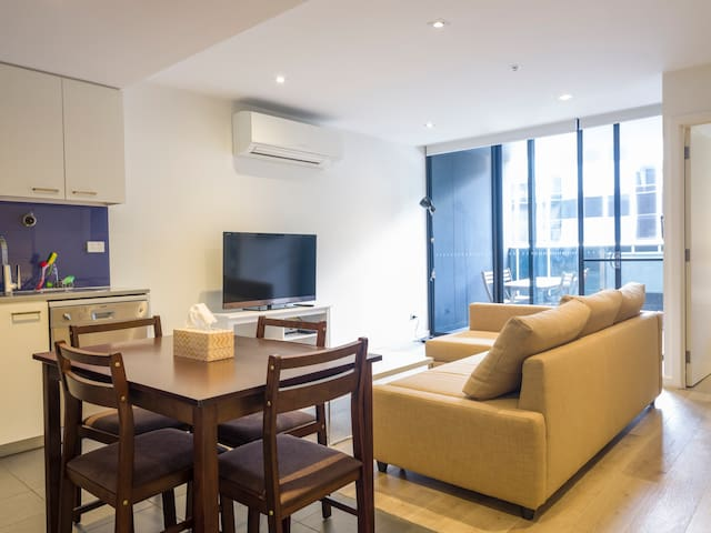 Kitchen and Lounge Area with Sofa Bed 4K Smart TV, High Capacity Reverse Cycle Split Air Conditioner System & Balcony.