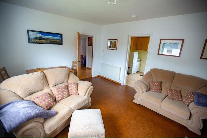 Living room with two sofas, dining table, TV and DVD player, and log burner