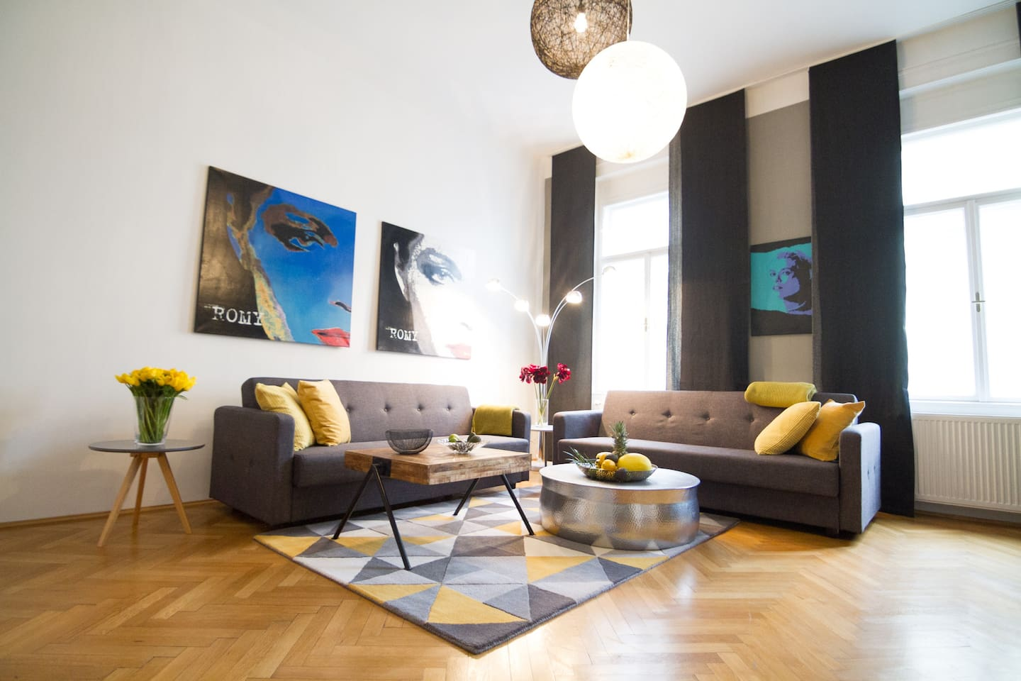Spacious and bright Living Room with 2 Bed Couches, high ceiling, herringbone floors.