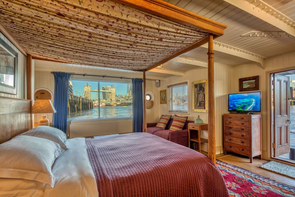 Tower Bridge Houseboat: Master Cabin 1. Remote controlled electric curtains reveal the view from the Heal's 1920's oak four poster bed