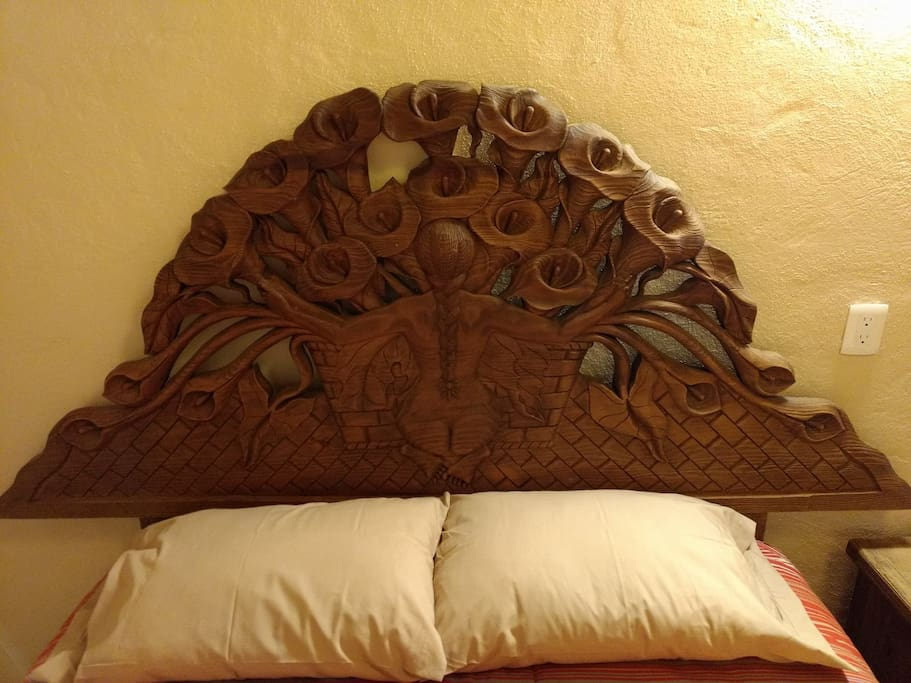 Headboard of the bed with a work by Diego Rivera hand engraved in wood.
