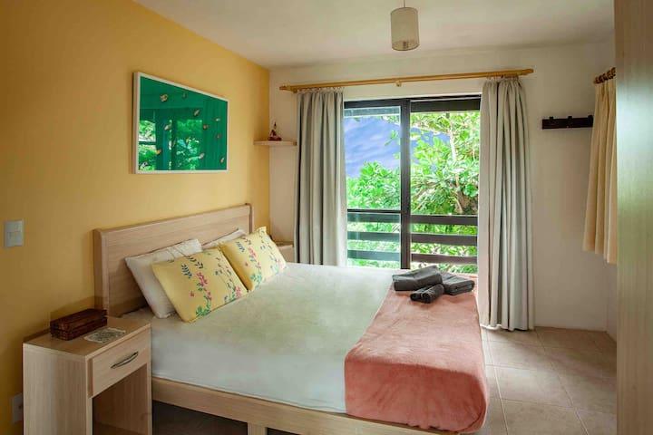 Suíte. Iluminada pela luz natural da tarde, é um quarto amplo e de cor amarela suave, sendo muito acolhedor para o descanso.
