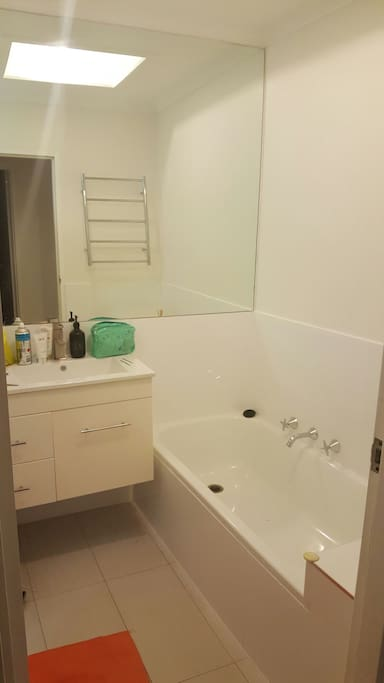 Bath and shower with a large wall to wall mirror.