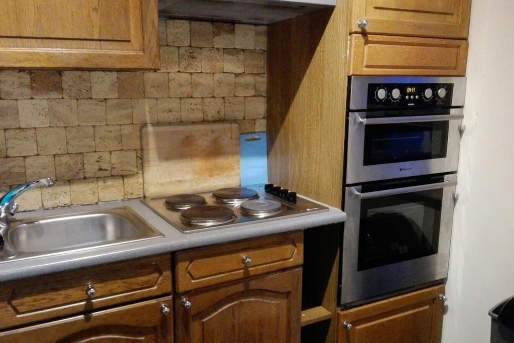 Rear view of the kitchen with sink, 4 cook fires, 2 ovens (small and big with grill) and storage space available.