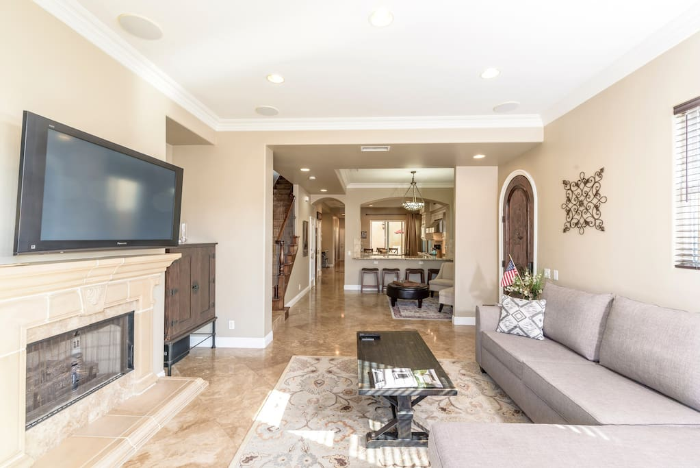 1st floor great room; front living/entertainment space off front patio; sitting area, kitchen, stairway to upper floors, middle patio; big screen TV and gas fireplace; stone floors; granite counters; half-bath
