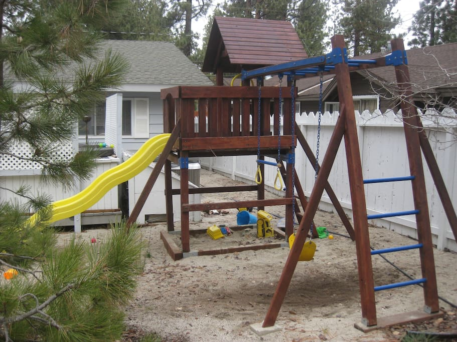 There is a giant swing set with slide and fort for the kids.