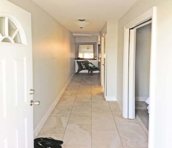 Wide-angle view of front hallway.  This apartment features cool tiled flooring throughout.