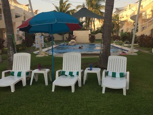 Tumbonas, toallas, mesas y sombrilla en área de alberca para uso exclusivo de usuarios del departamento