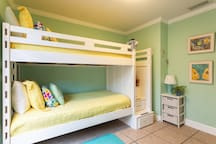 The Go Bunkers bedroom is decorated in tropical colors and has a twin bunk bed combination and an adjacent full bathroom.