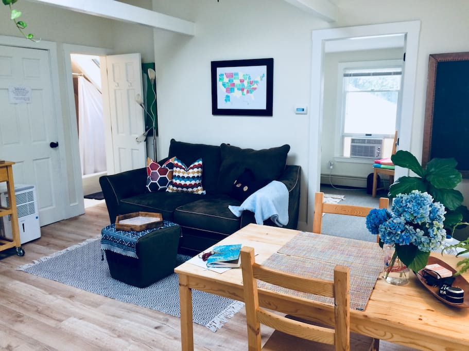 Plenty of comfortable seating in the main room.  Bathroom and bedroom both open up to the living area with high ceilings, large skylight and well-loved plants.