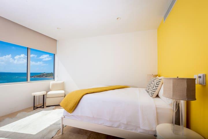 1 of 2 queen bedrooms with ensuite bath and ocean view.