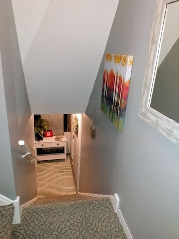 Stairs to lower level upon entering the house from the garage. Suite is at the bottom of the stairs on the right. The console table has local menus in the drawer,  first aid kit, smoke detector. A fire extinguisher is in the closet at top of stairs.