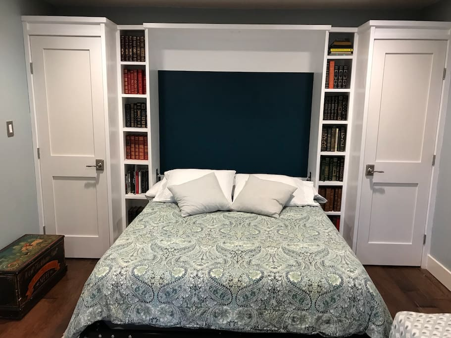 Queen-sized Murphy bed surrounded by a beautiful library
