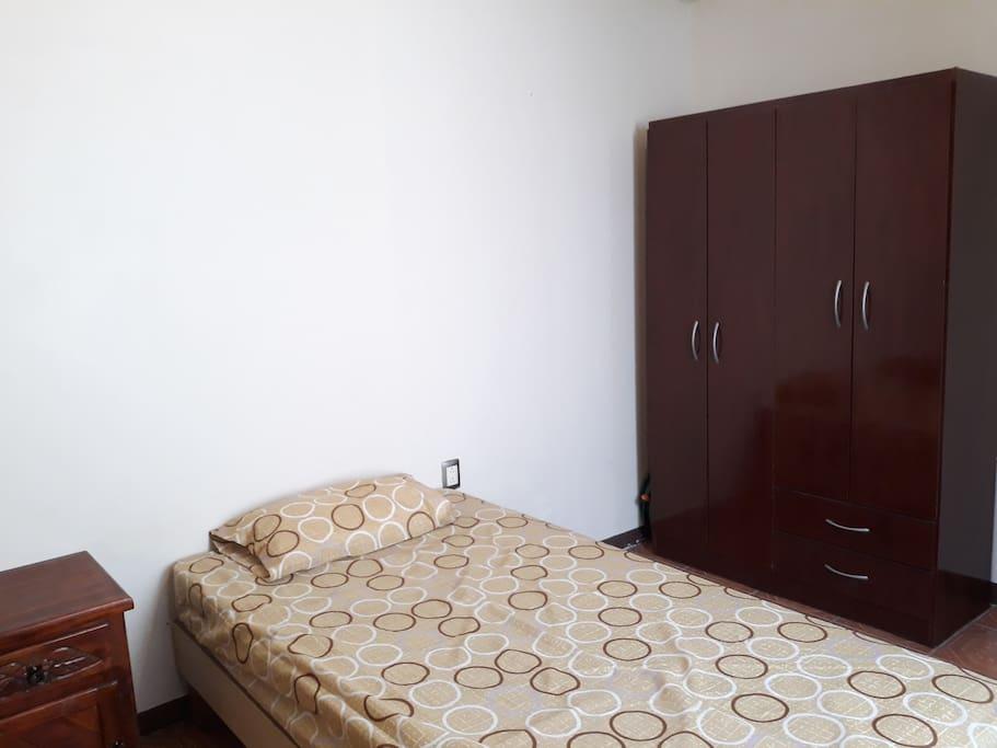 Habitación 1, cuenta con cama individual, mesa de noche, ropero y ventana  ubicada en planta baja.