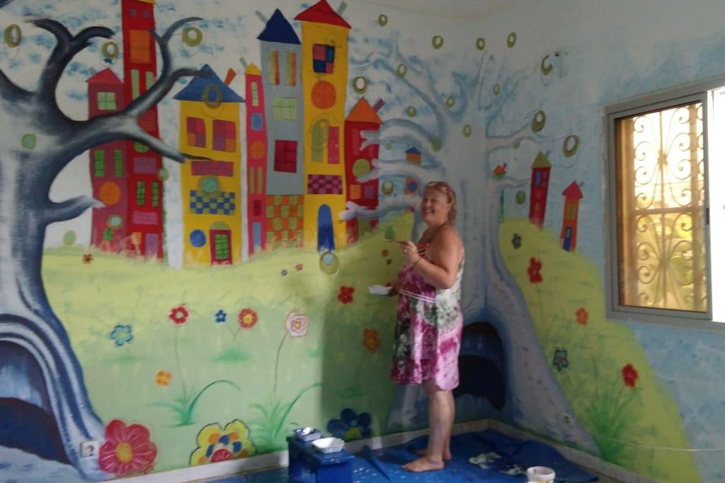 en cours de peinture dans la chambre caméléon, avec un paysage pop art inspiré de Hunderwasser et de l'exposition que j'ai vu avec ma fille a l'atelier des lumières à Paris sur Klimt et Hunderwasser...je n'ai pu résister ! avec le coté sénégalais avec les baobabs en premier plan !