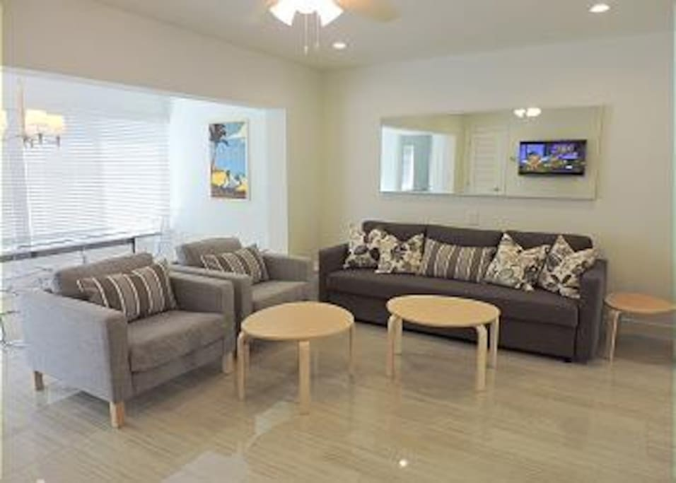 COMFORTABLE LIVING ROOM WITH QUEEN SIZE SOFA BED AND LARGE FLAT SCREEN HD TV
