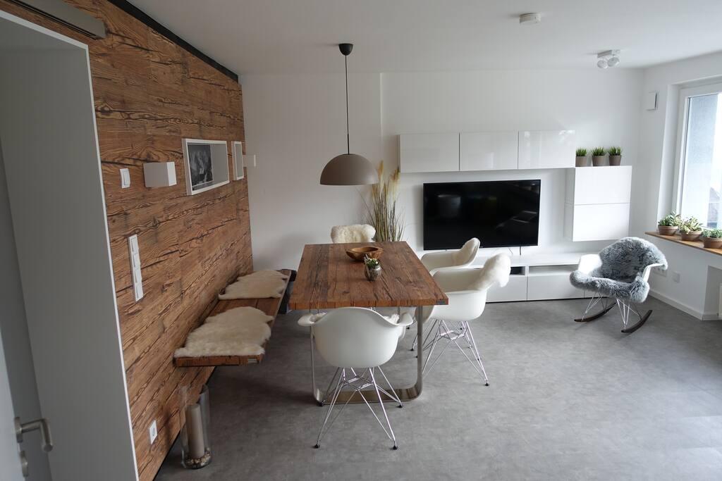 Wohnzimmer mit Naturholzsitzbank, 4 Stühlen und Schaukelstuhl