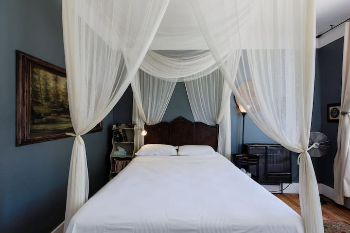 Queen bed with mosquito net in honor of W. Somerset Maugham.