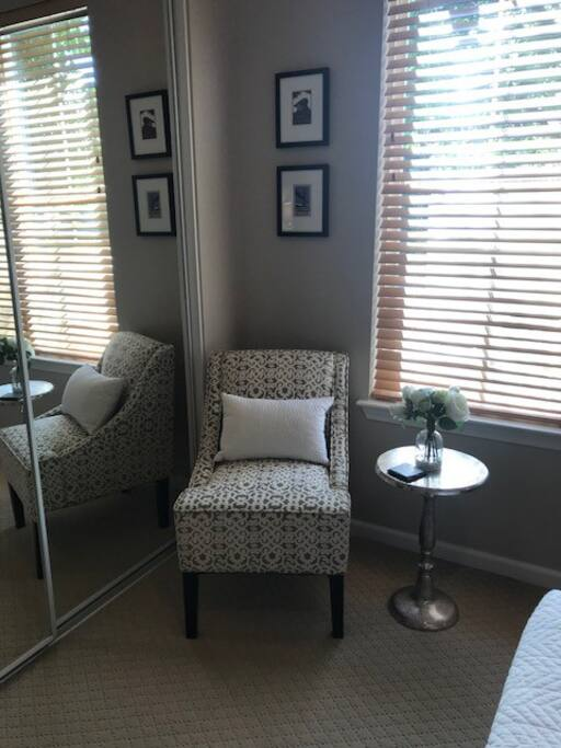 Mirrored closet doors and a small chair & table.