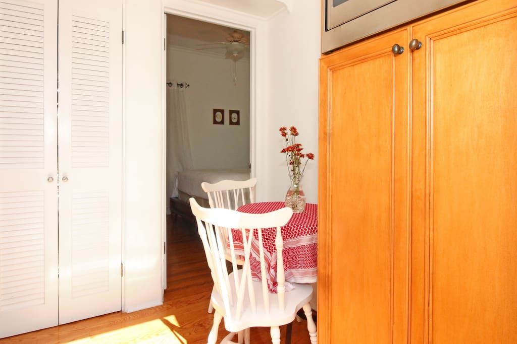 Adjoining shared laundry room and breakfast nook with washer and dryer behind the louvered doors.