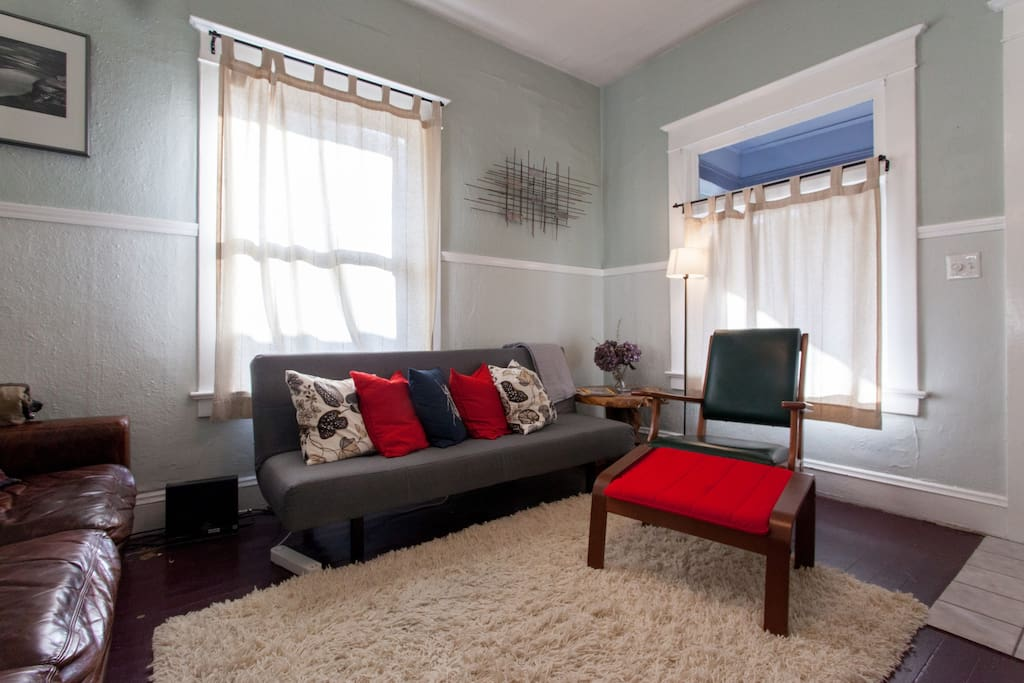 Cozy living room with futon that sleeps one adult
