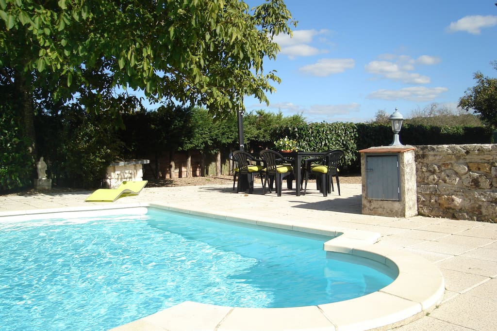 pool and seating area including sun chairs and tables