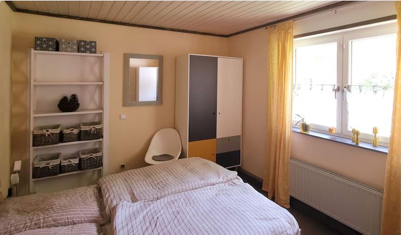 Schlafzimmer mit Doppelbett, zwei großen Schränken und Spiegel