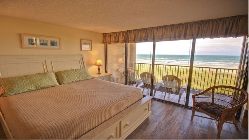 King size bed with floor to ceiling view of the beach.