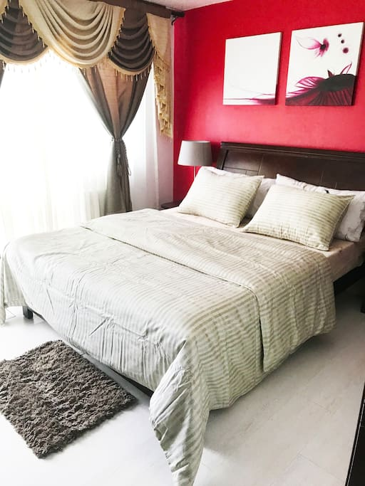 Master Bedroom: Equipped with a window type air con, Queen size bed, flat screen tv, chandelier with a beach view.