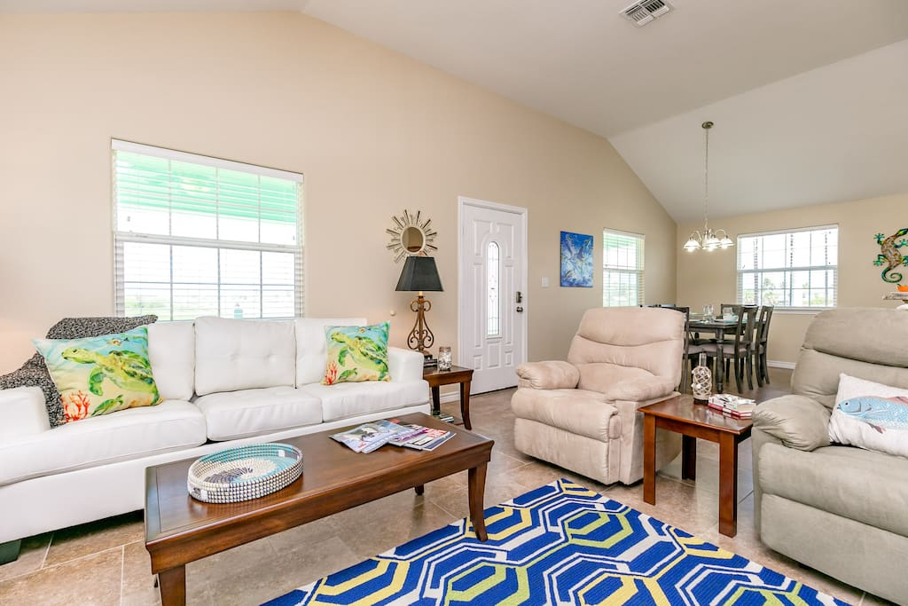 An open living room has plenty of comfortable seating around a flat-screen TV.
