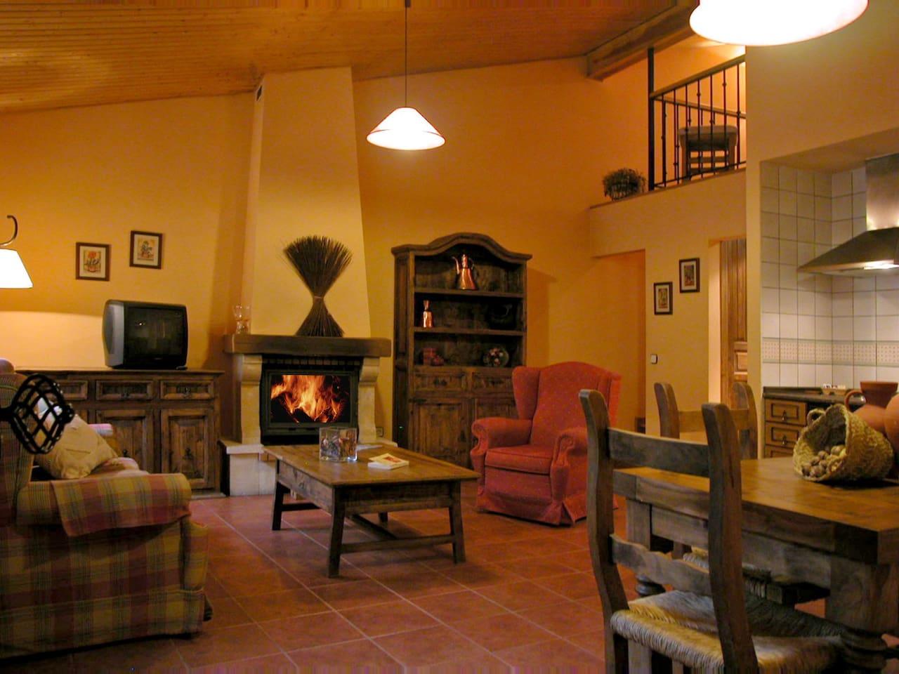 Salón con chimenea y cocina.