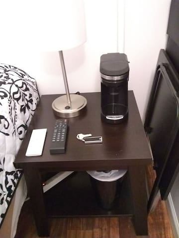 Bedside table with coffee machine, TV remote, Air conditioner remote and key to your room. Folding chair and table fit next to the bedside table.