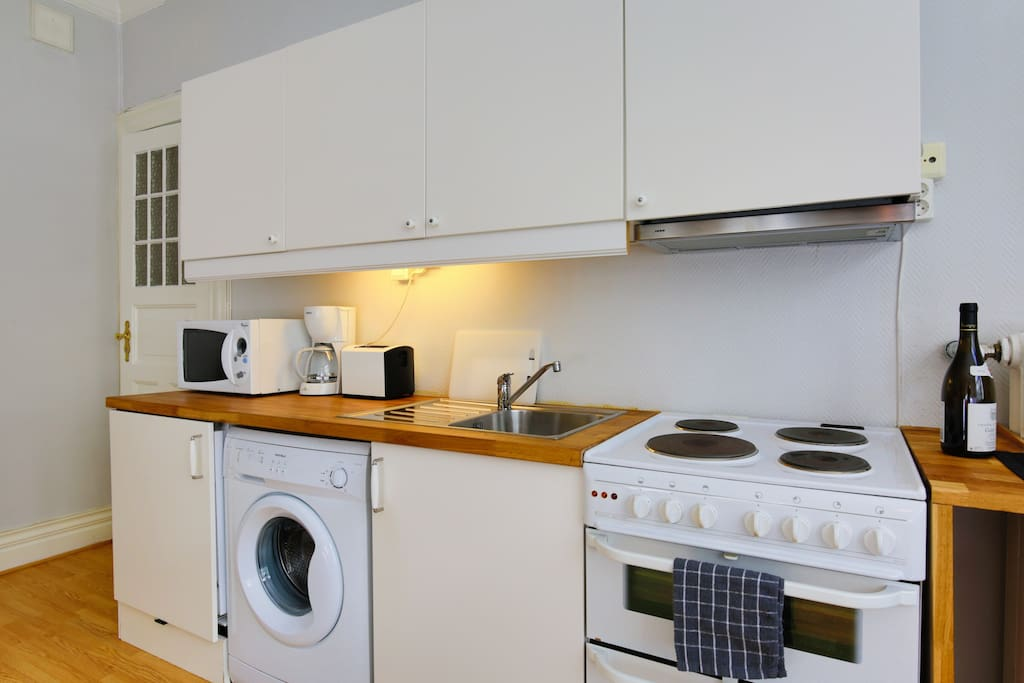 Kitchen area with stove, dishware, clothes washer, microwave, refrigerator and more. Enjoy a selection of coffee and tea as well!