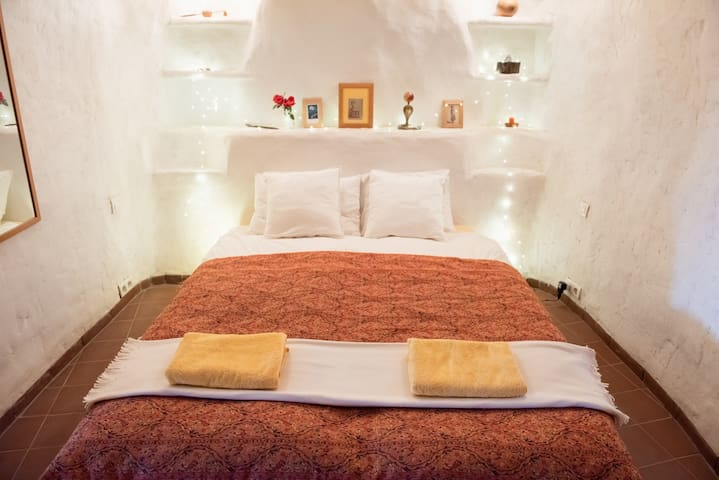 The cave bedroom has a kingsized bed, a chair and drawers and hanging space. It is in the deepest part of the cave and is quiet and tranquil, promoting a good nights sleep.