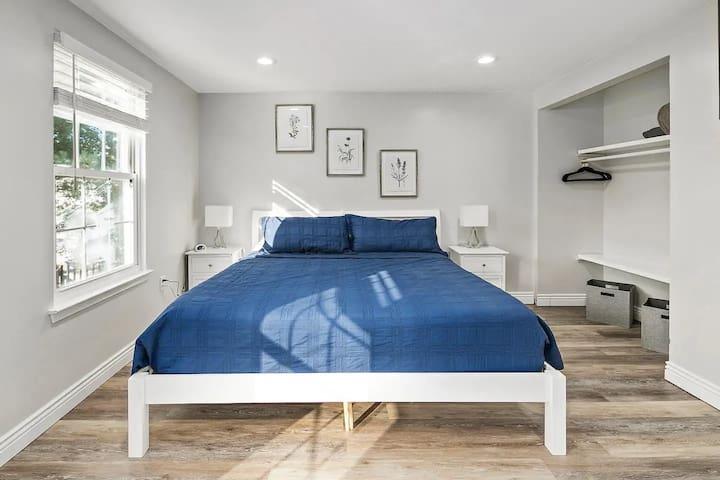 The master bedroom also has a wall mounted flatscreen TV.