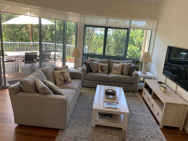 Very comfy lounge opening onto middle deck with outdoor setting and BBQ