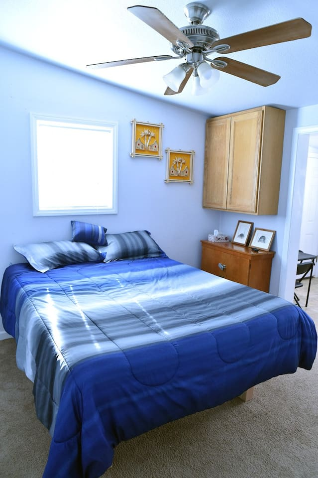 Queen size bed with sunny west facing window with blinds