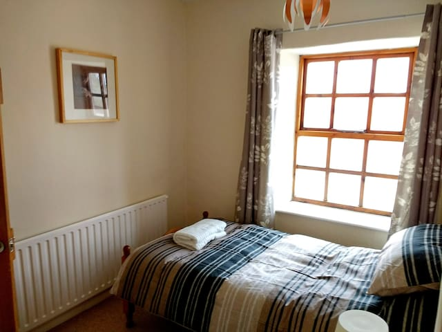 Second bedroom with single bed and cupboards for storage.