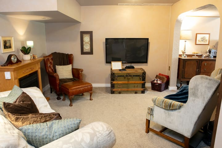 """Relax in the cozy living room area with a 51"""" satellite TV, electric fireplace, and library."""