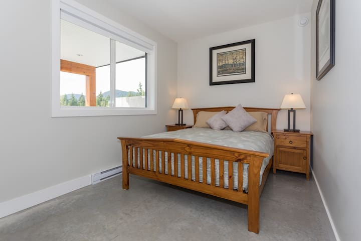Bedroom 1 includes a Queen size bed, which sleeps 2 adults comfortably, with views down to Howe Sound.
