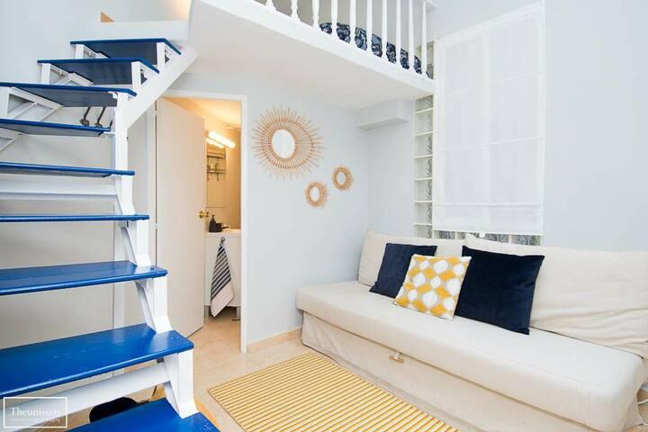 Distribución del estudio-loft con el colchón individual (105cm) en el altillo y el baño completo debajo y espacio salón con sofá cama y mesa de comedor con 2 taburetes