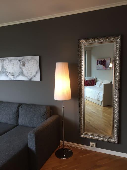 Sovesofa og brisk (i speilbildet) i stuen