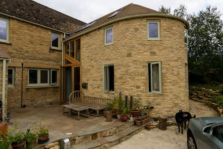 Double bed in a curved Cotswold cottage near train