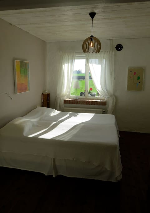 Lugnt och svalt sovrum mot trädgård och åker.